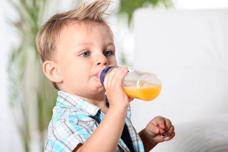 Niño tomando zumo de mandarina